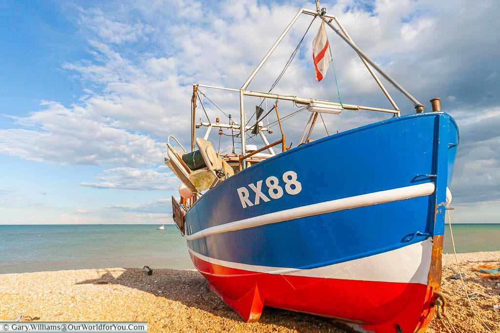A small brightly coloured red, white & blue fishing boat on the beach at Dungeness, Kent