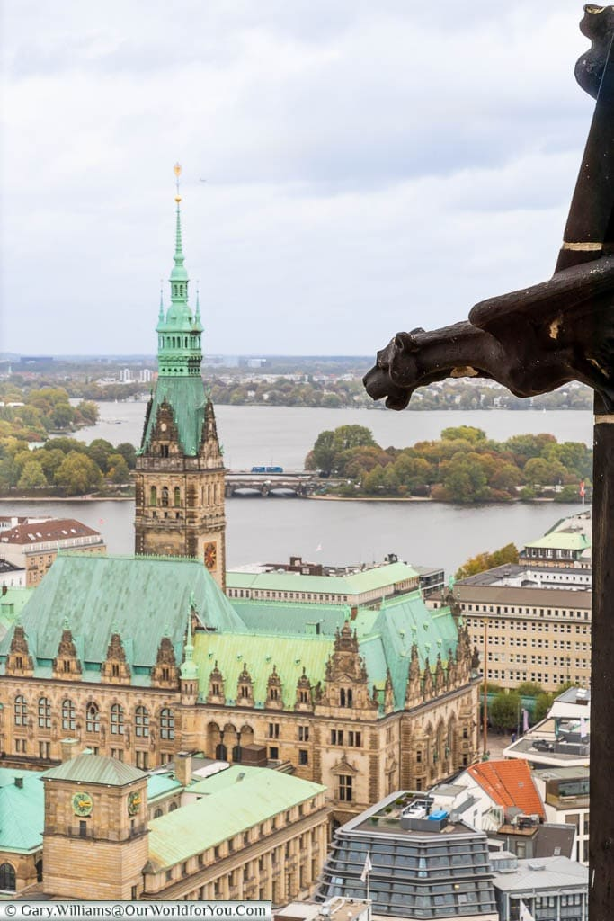 A view from the neo-gothic St Nikolai-church tower across the Rathaus to the been Binnenalster and beyond.  On the right of the frame is a gargoyle, part of the tower structure.