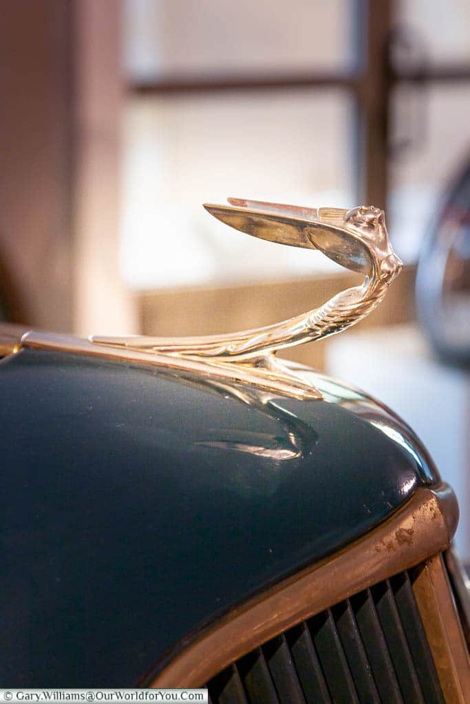 A close-up of a car bonnet/hood ornament of an art deco design in the Museum of Automotive History in Salamanca, Spain