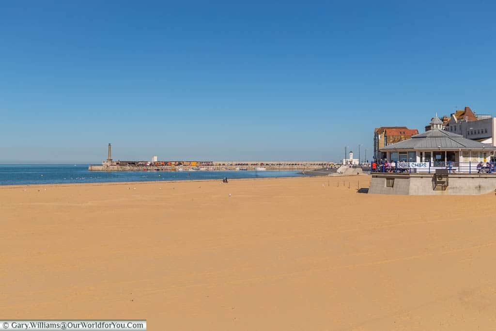 The golden sand of Margate's main beach, with a fish 'n' chip shop in the foreground.  Margate's harbour arm can be seen in the distance.