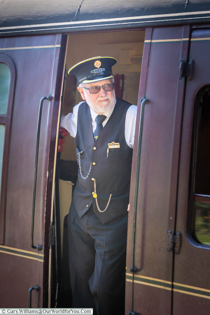 A well-dressed guard is standing in the doorway of the guards' carriage as a steam train prepares to depart the Sheringham station on the North Norfolk Railway.