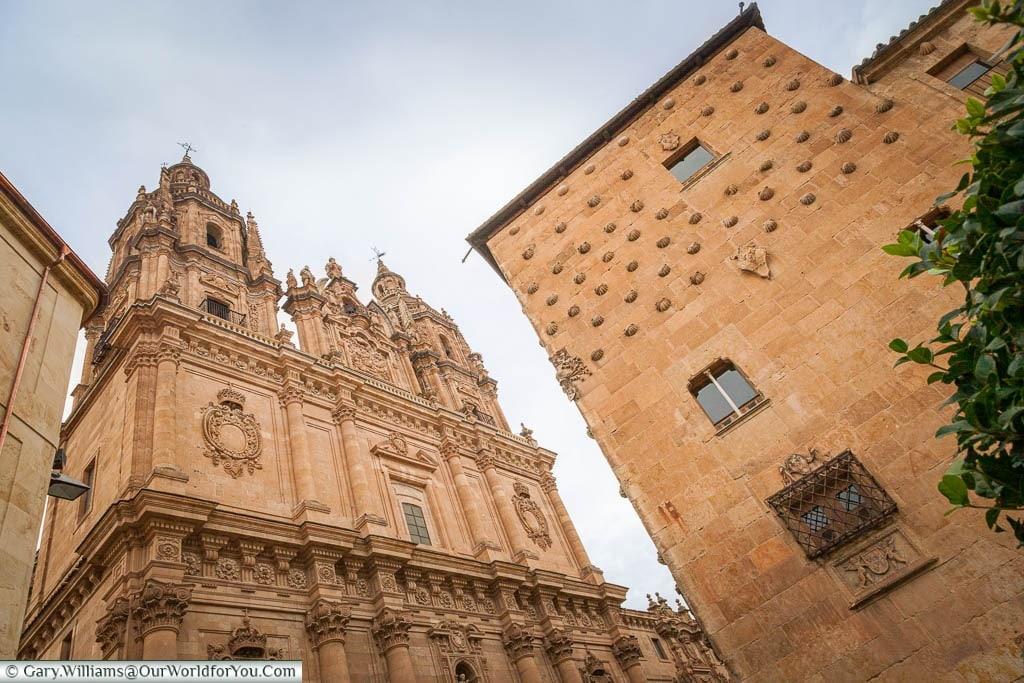 La Clerecía cheuch in a Spanish baroque style & the edge of Casa de las Conchas in Salamanca, Spain .