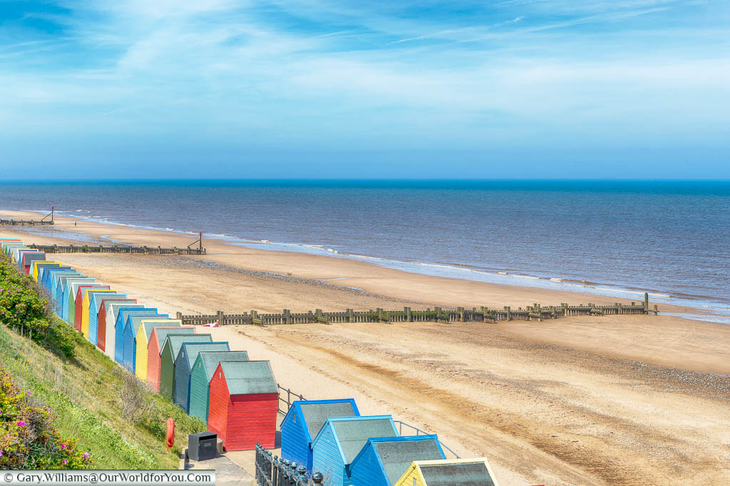 A line of colourful beach huts line the edge of the golden sands at Mundesley Beach on the North Norfolk Coastline
