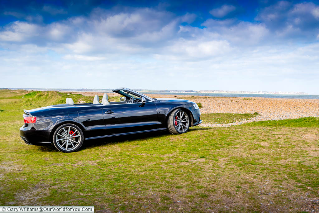 Our black Audi convertible parked up n a grass verge overlooking the coast near Sandwich in Kent as we embark on a Kentish Coastal Road Trip.