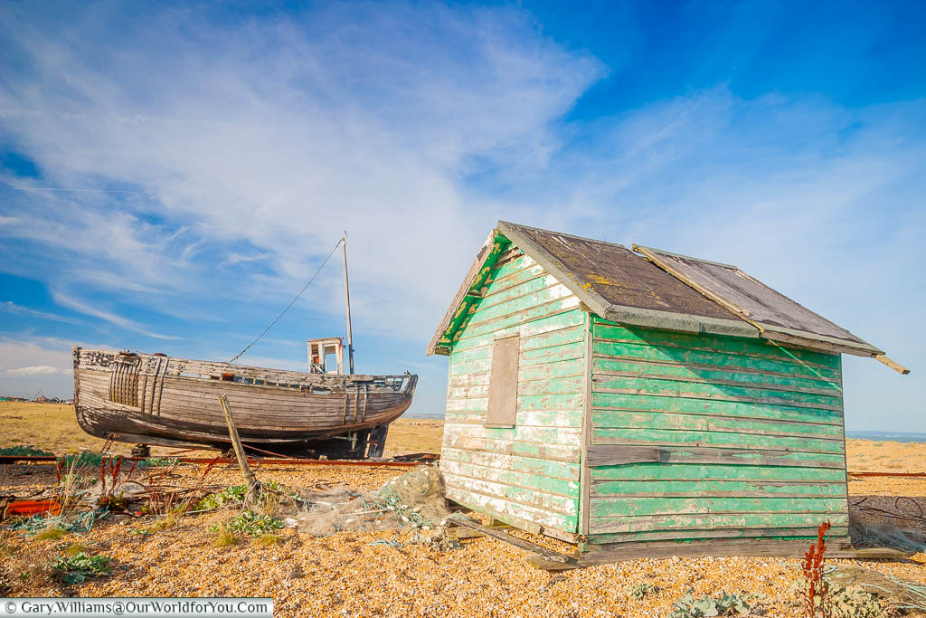 A small decaying wooden fishing boat next to a fisherman's hut on the shingle beach of Dungeness