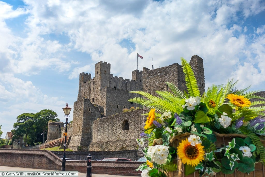 Looking up at Rochester Castle from the bottom of Boley Hill from behind a flower display