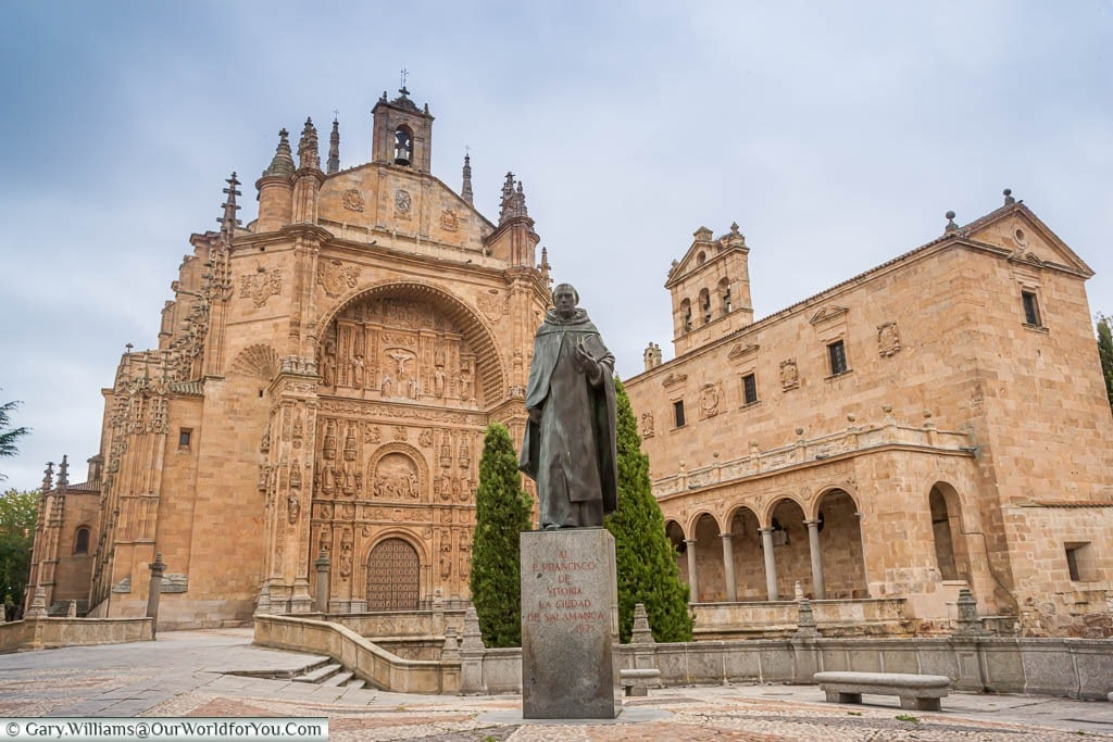 A statue of a monk outside the gothic Convent of San Esteban in Salamanca, Spain