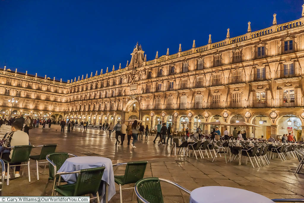 Tables & chairs outside restaurants in the Plaza de Mayor at dusk