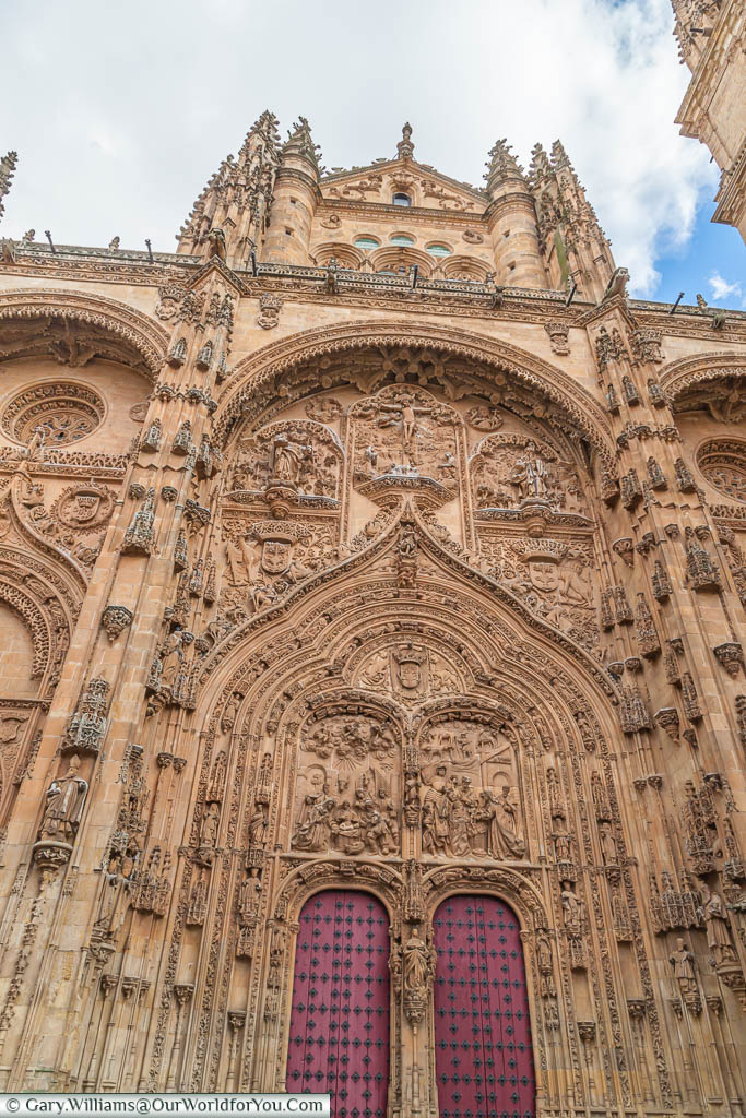 Two heavy red doors in the gothic facade are the entrance to the old Cathedral in Salamanca, Spain