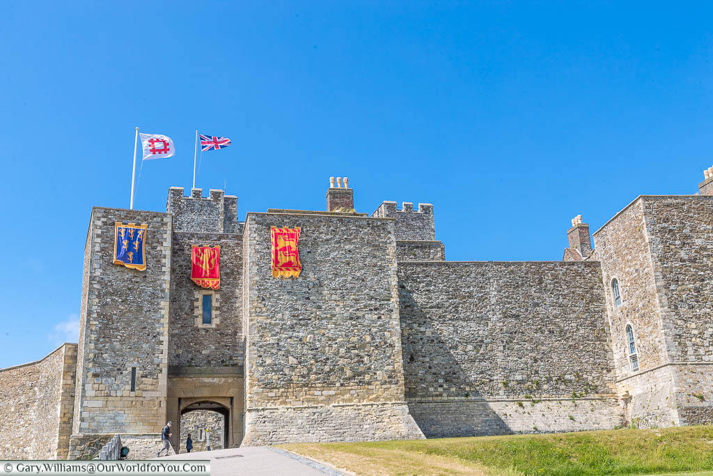 Dover Castle's outer walls draped with the standards of Henry II, and flying the flags of English Heritage & the Union Flag.