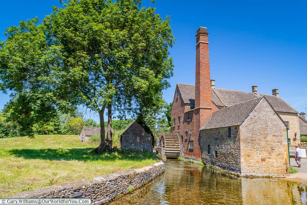 An idyllic Cotswold scene of the watermill  in Lower Slaughter under a deep blue sky