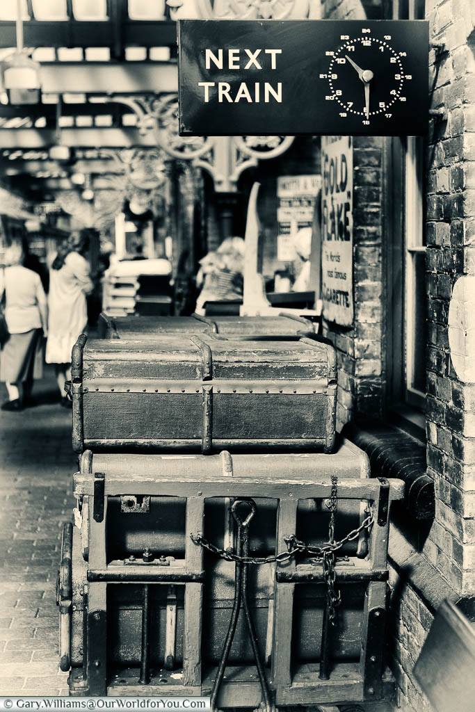 A nostalgic black and white image of a stack of traditional suitcases under a signed for the next train at the Sheringham station of the North Norfolk Railway.