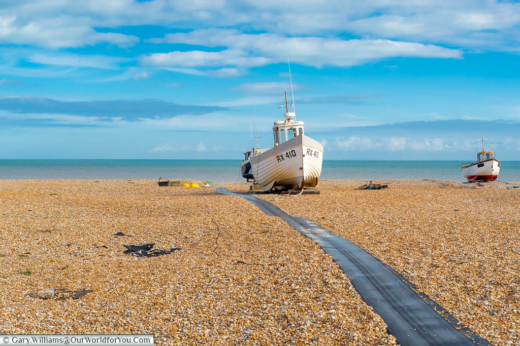 A couple of small fishing boats on the cobbled beach of Dungeness
