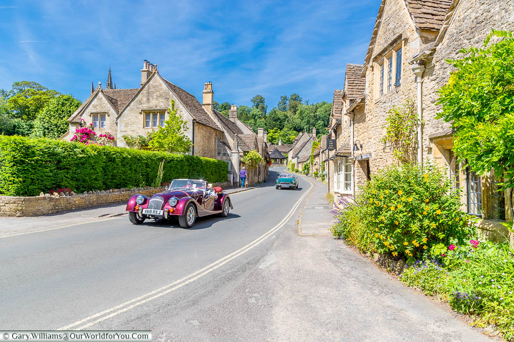 A classic Morgan sports car driving through the Cotswolds village of Castle Combe
