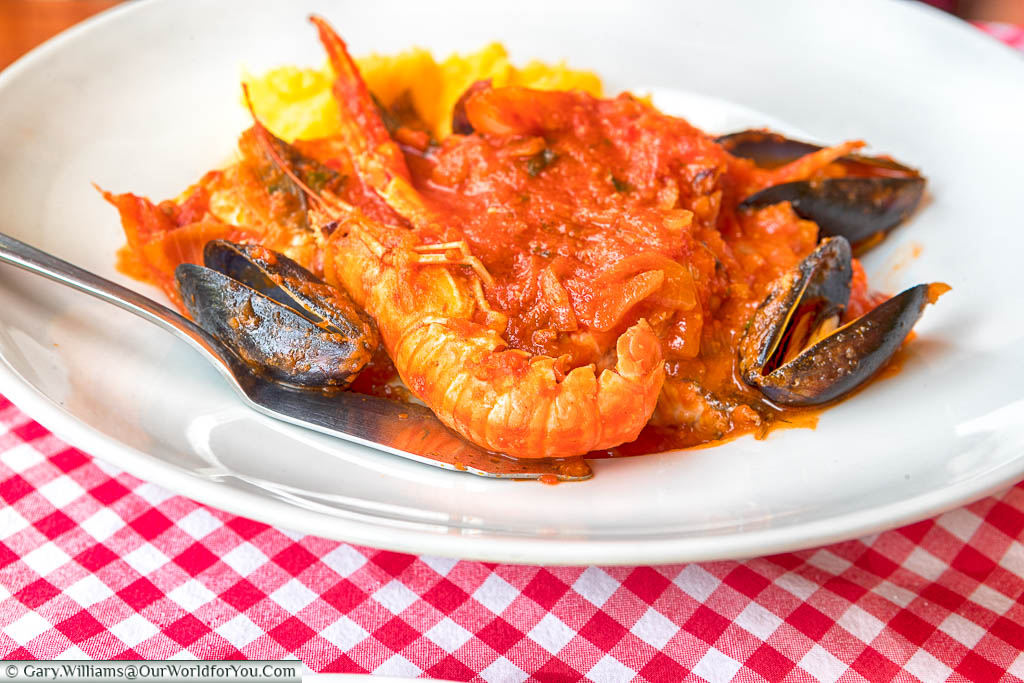A Croatian seafood brodet stew consisting of giant prawns & muscles in a tomato sauce, served with polenta