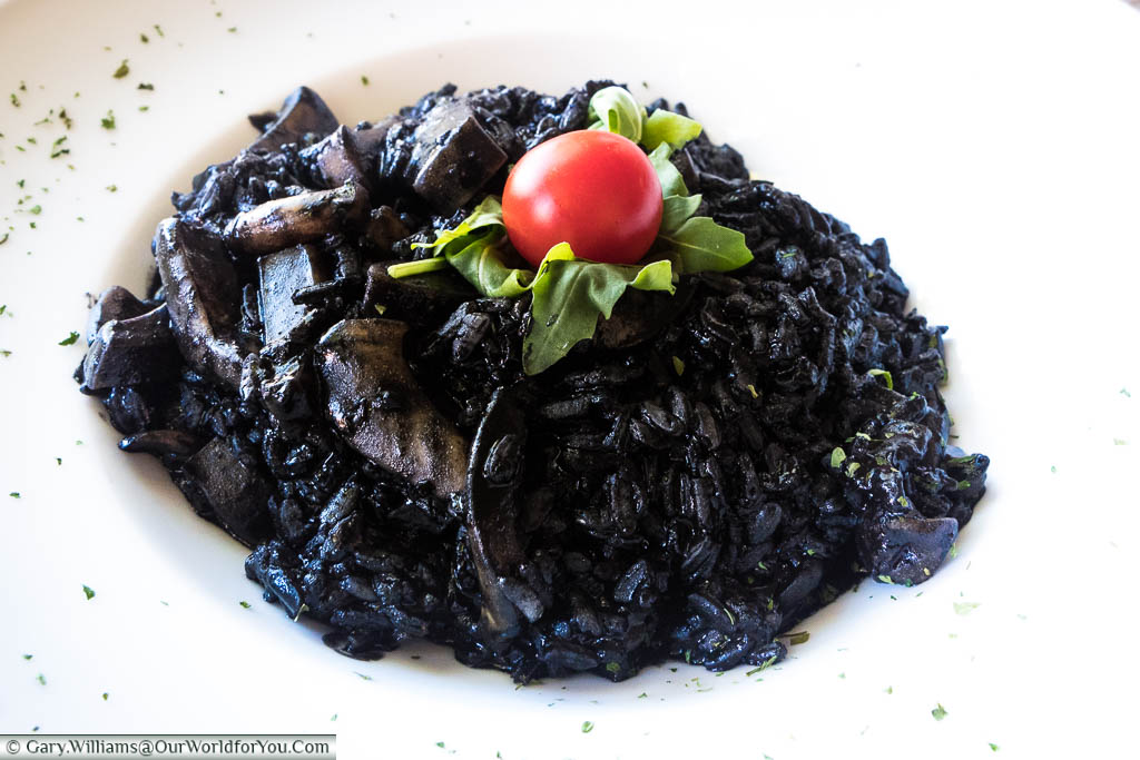 An ink-black cuttlefish risotto, topped with a green salad leaf, and a bright red tomato