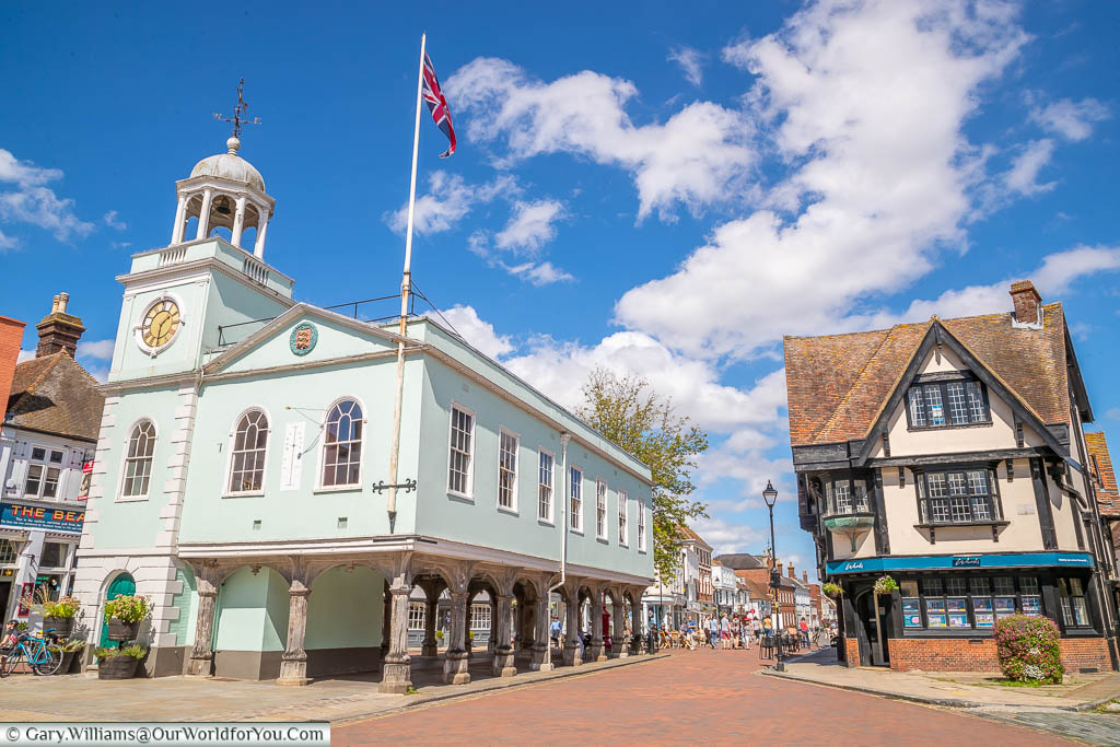 The pale green historic Faversham Guildhall stands proudly in the centre of the Market Square displaying a Union Flag fluttering on a bright sunny day.