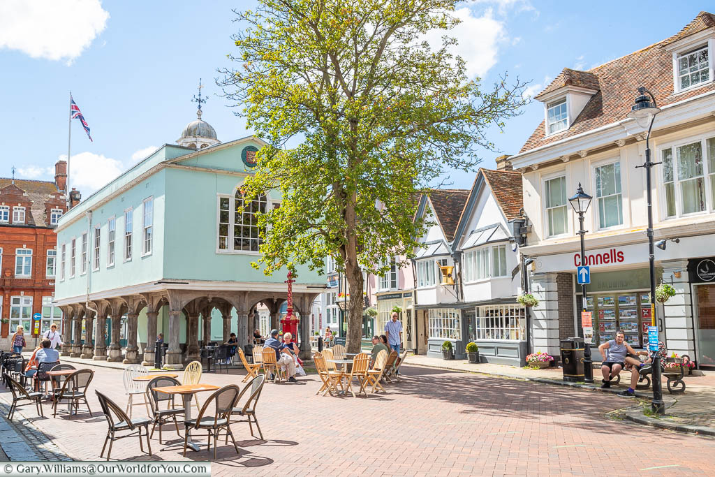 A view of Faversham Guildhall from Court Street) with tables & chairs outside cafe's on a bright sunny day