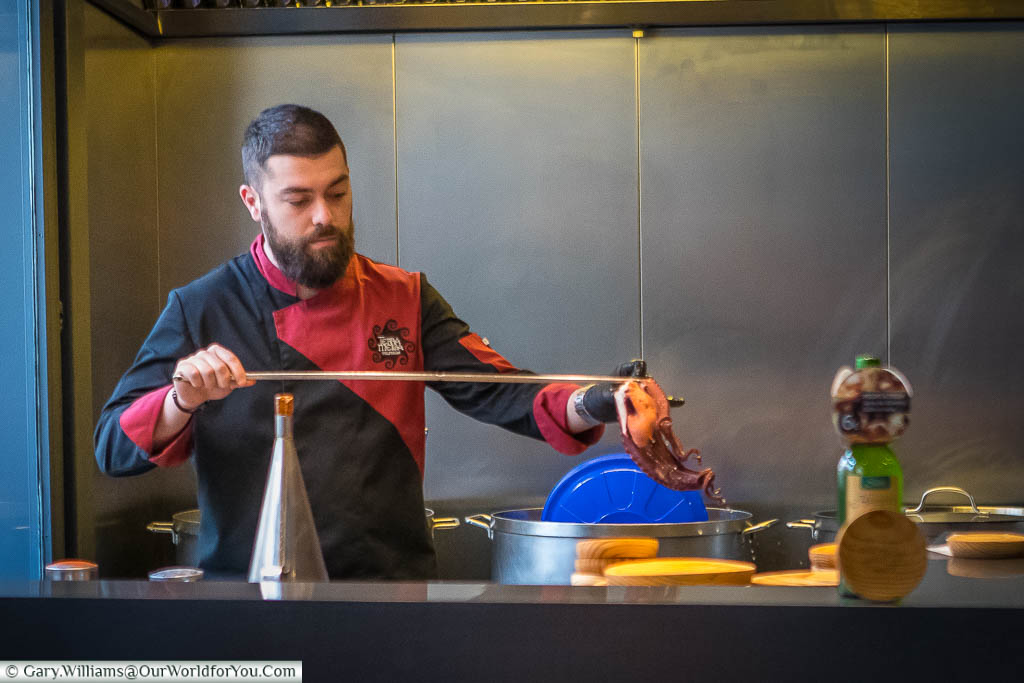 A Spanish chef, pulling a skewered octopus from a pot of boiling water