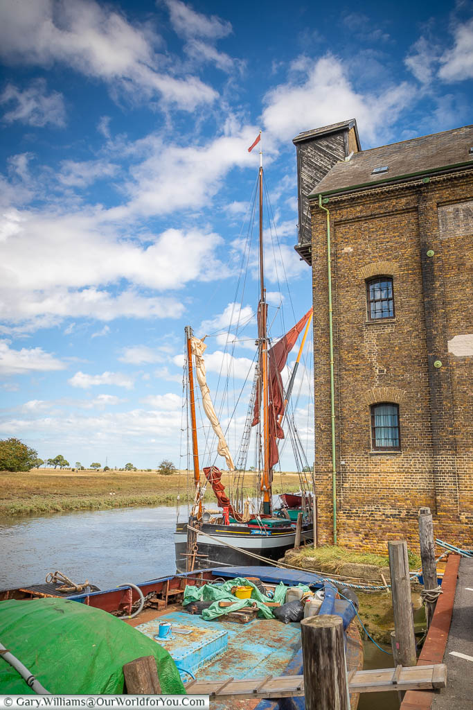 An old sailing barge moored next to the Oyster Bay House on Standard Quay in Faversham, Kent