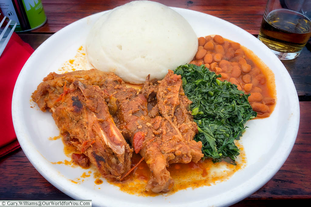 A plate of a rustic beef stew, with green leaves, beans & the Zimbabwean staple, sudza.