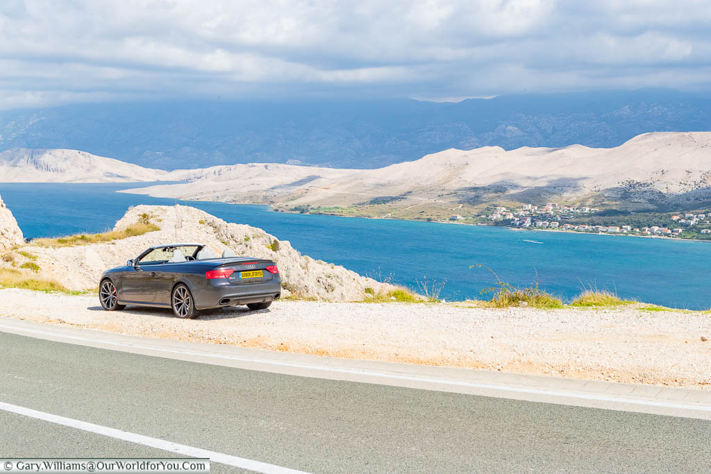 Our Audi convertible parked up overlooking the blue waters of the Adriatic on our way to Pag on our Croatian Road Trip
