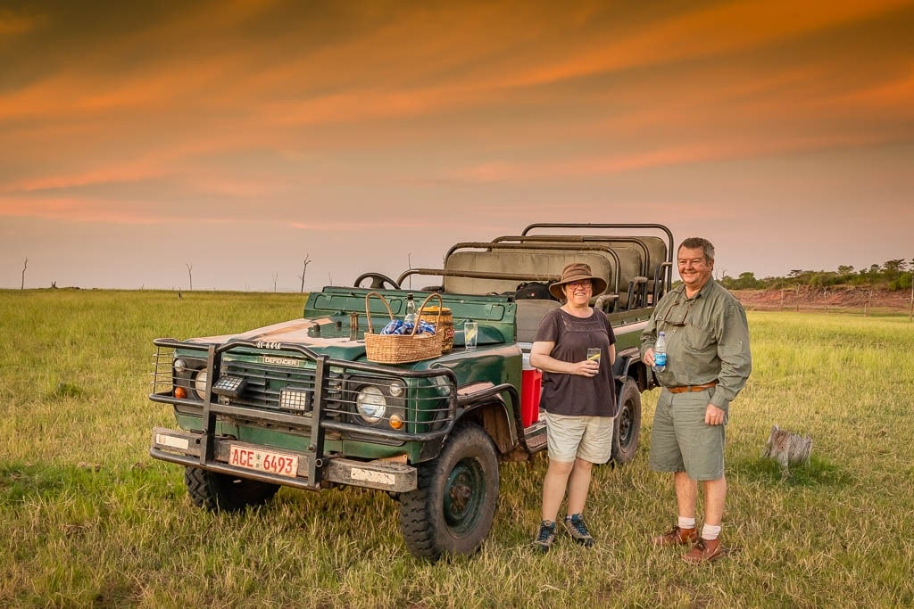 Janis and our guide Mark chat next to our trusty Landrover during a break on our evening safari drive at Rhino Safari Camp next to Lake Kariba in Zimbabwe