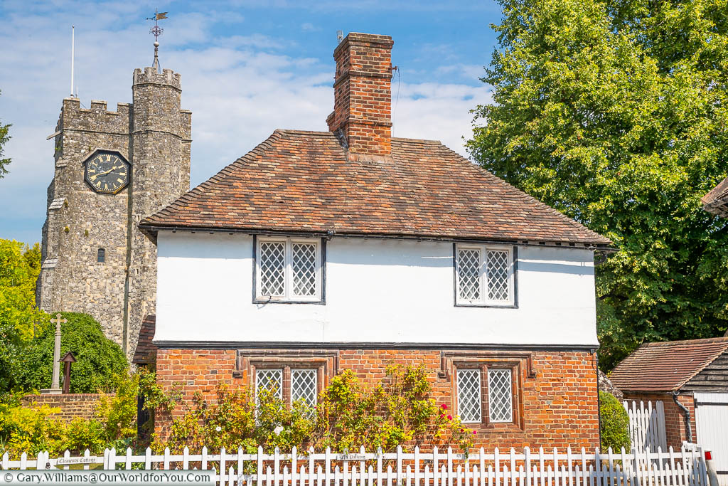 A pretty little house behind a white picket fence, with Chilham's church clock tower in the background.
