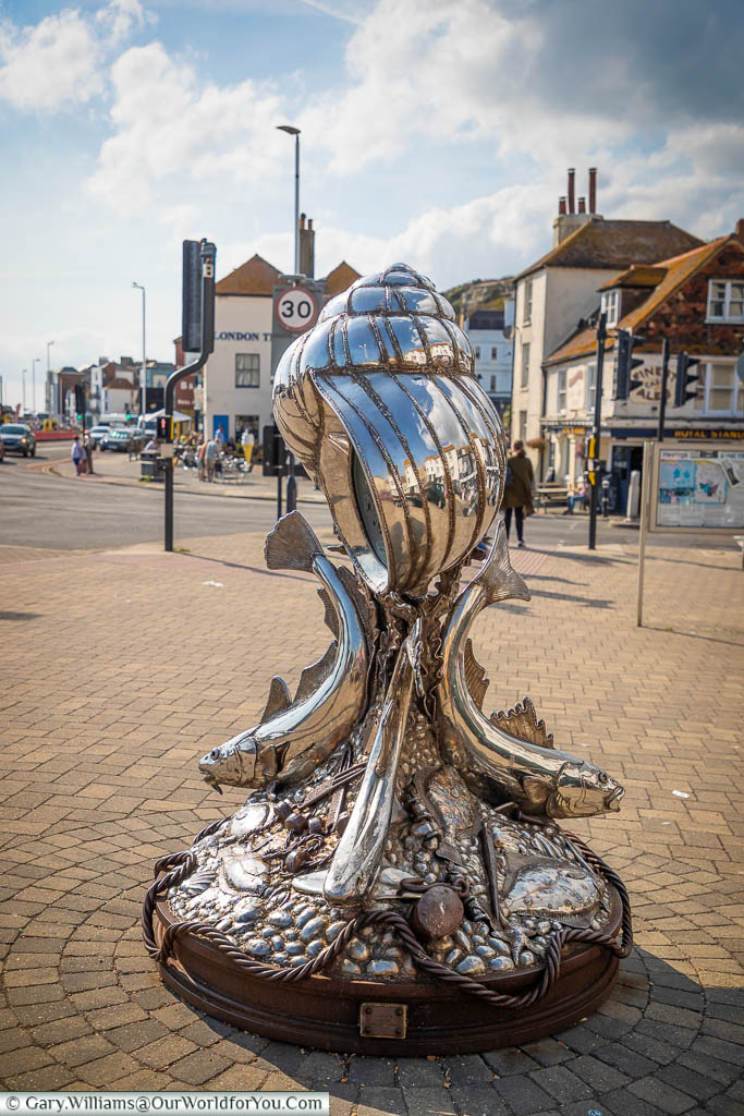 A polished steel sculpture of a giant winkle (sea snail) supported by fish at the point the old town of Hastings meets Rock-a-Nore