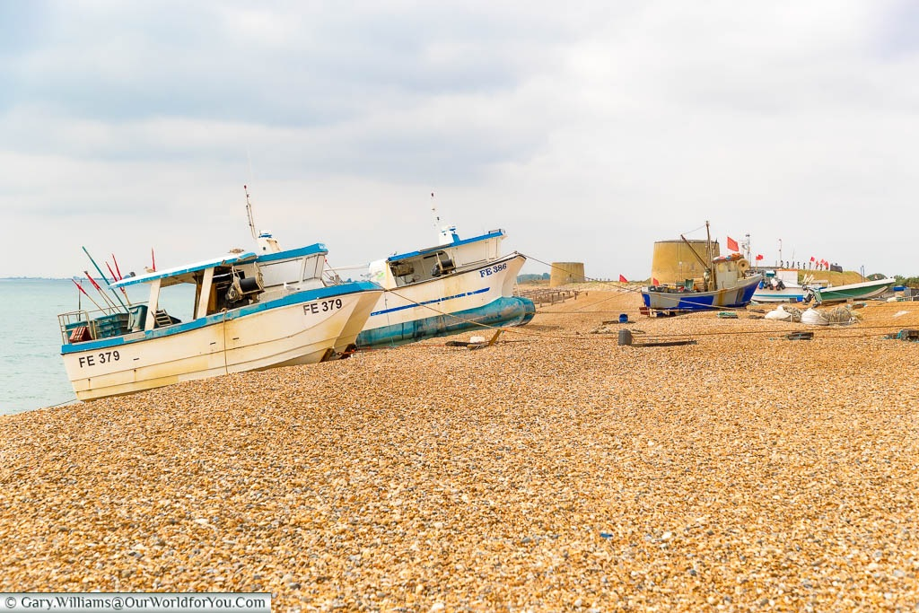 A beach scene from Hythe with fishing boats landed on the shale, and the Martello Towers in the background