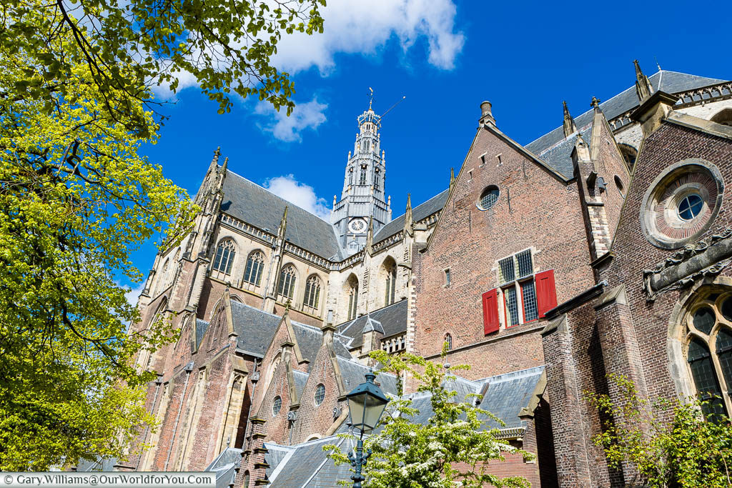 Looking up from street level to the grey spire of red-brick St. Bavo Church in the centre Haarlem