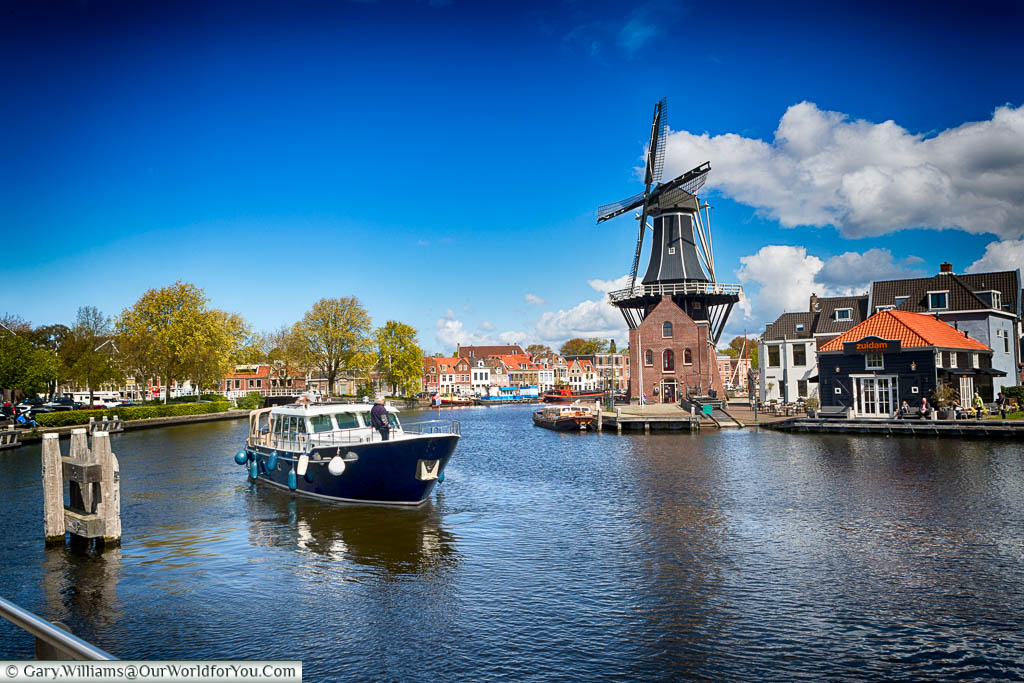 A medium-sized blue boat navigating the canal in front of the restored Windmill De Adriaan in Haarlem