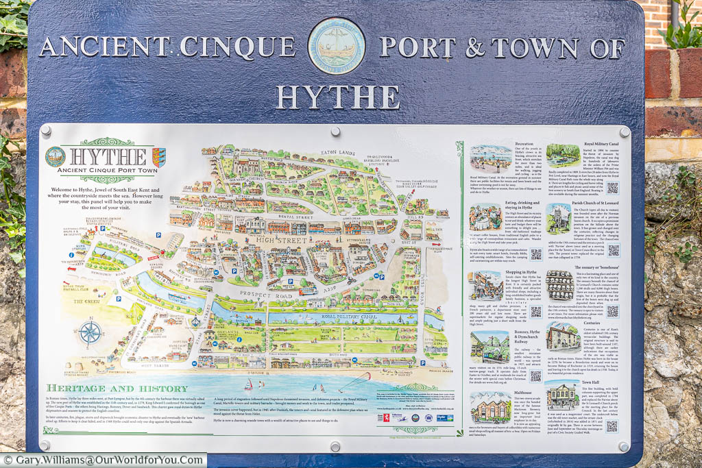 A tourist information board on the street with a map of the old town and key points of interest in Hythe