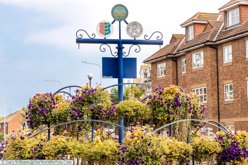 A roundabout decorated with flower baskets at the entrance to Hythe displaying signs for the town, its status as a Cinque Port and one from the Small Arms School