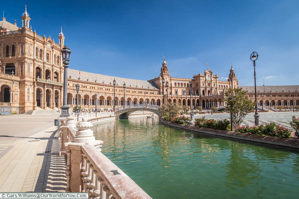 A view of the walkway next to the canal in the Plaza de España, next to the ornate buildings that surround it.