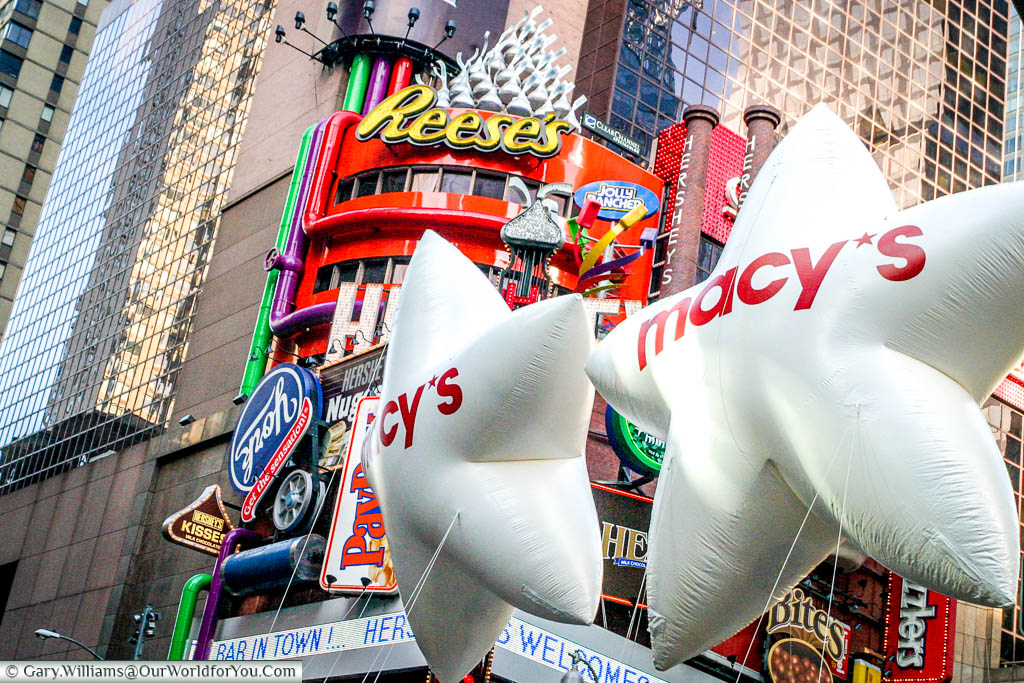 Two white inflatable Macy's stars, against the backdrop of skyscrappers, as part of the Macy's Thanksgiving Day parade in New York