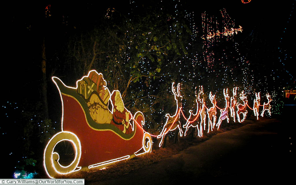 An illuminated Santa, his sleigh, and reindeers