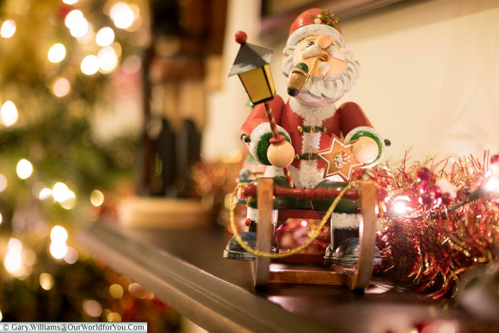 A German wooden Christmas decoration of Santa on his sleigh on our mantlepiece.