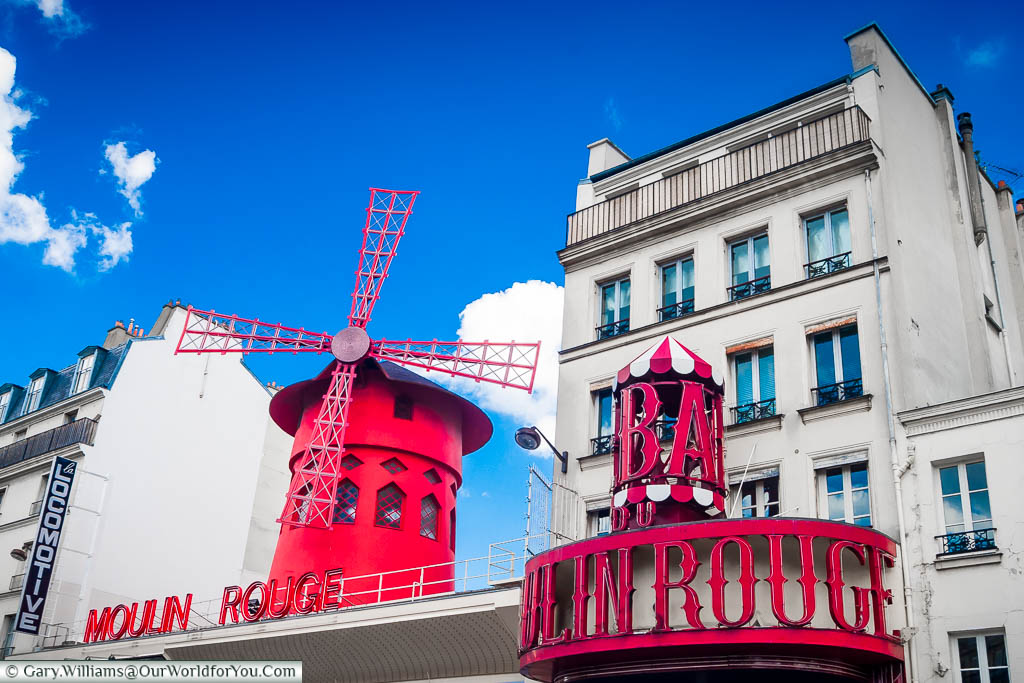 The roofline of the Moulin Rouge focusing on the bright red mill that takes centre stage set against a deep blue sky
