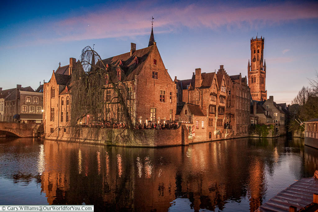 A view, at dusk, of the canals, and red brick medieval building of Bruges, with the Belfry in the backbround.