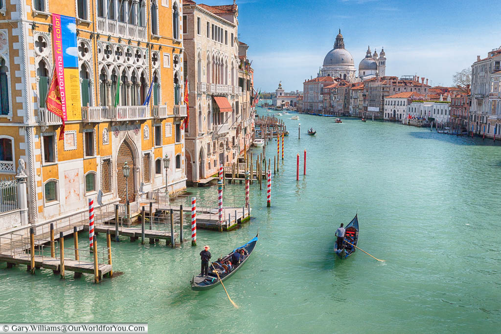 The view along the Grand Canal in Venice, complete with gondoliers,  towards the Basilica di Santa Maria della Salute from Ponte dell'Accademia