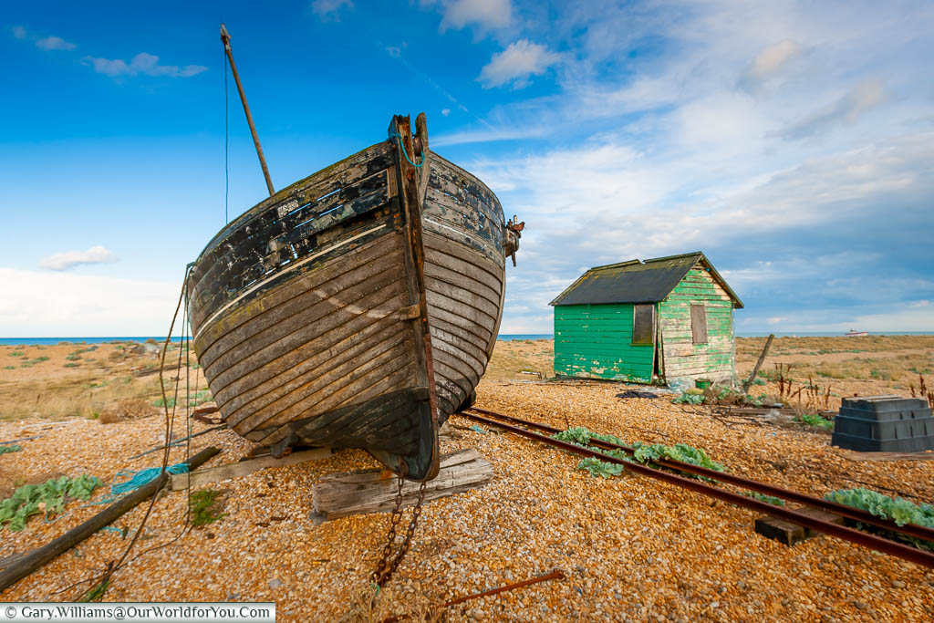 An abandoned fisherman's wooden trawler and dilapidated, green, wooden shack next to small track railway lines on the beach of Dungeness.