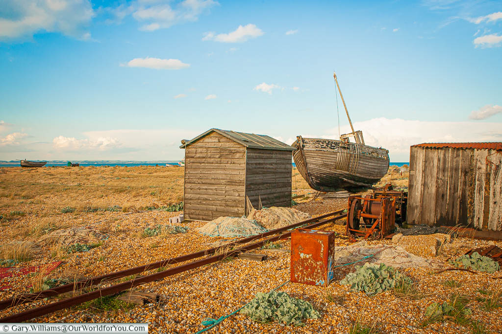A scene of abandoned fishermans' equipment including a wooden trawler, wooden shacks, rron winches and small track railway lines on the beach of Dungeness on the Kent coastline in England