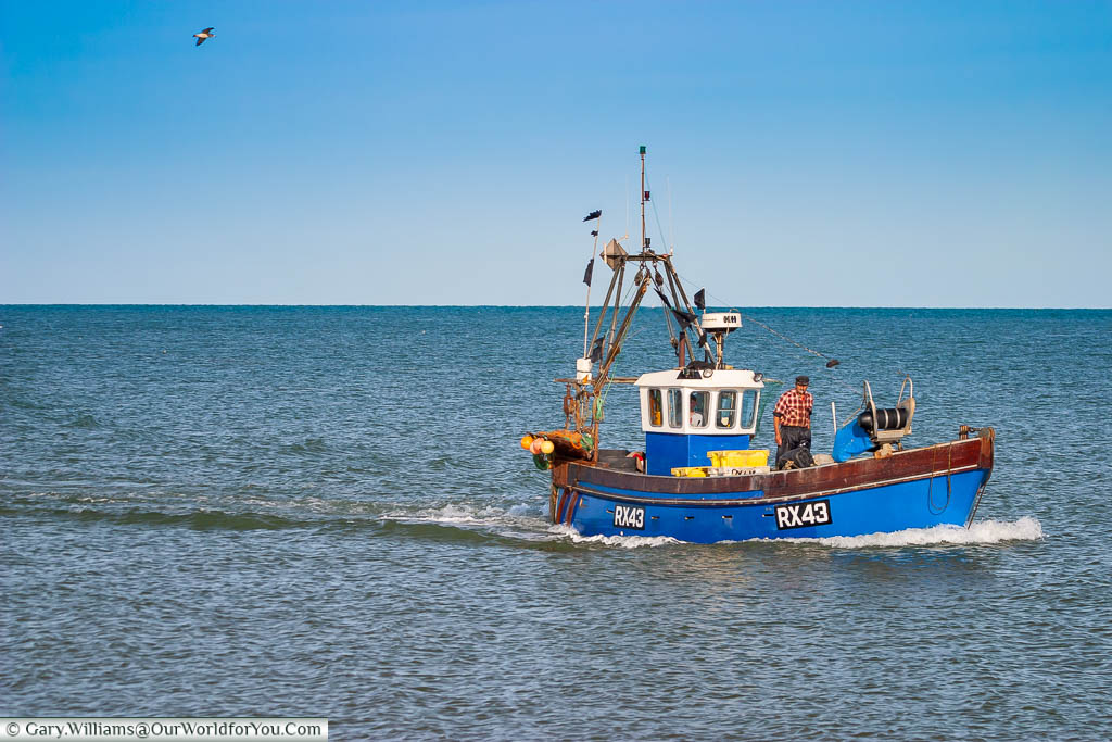 A small fishing trawler returning to the shore of Dungeness with its catch of the day