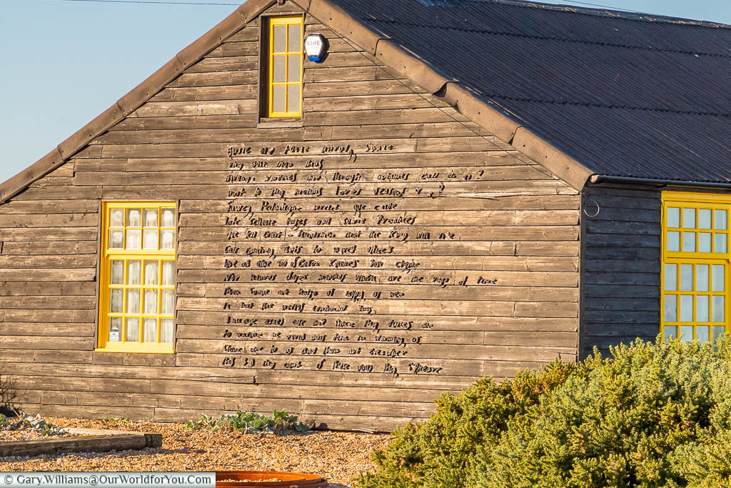 "Part of John Donne's poem, ""The Sun Rising"" in raised lettering on the side of Prospect Cottage on Dungeness Beach"