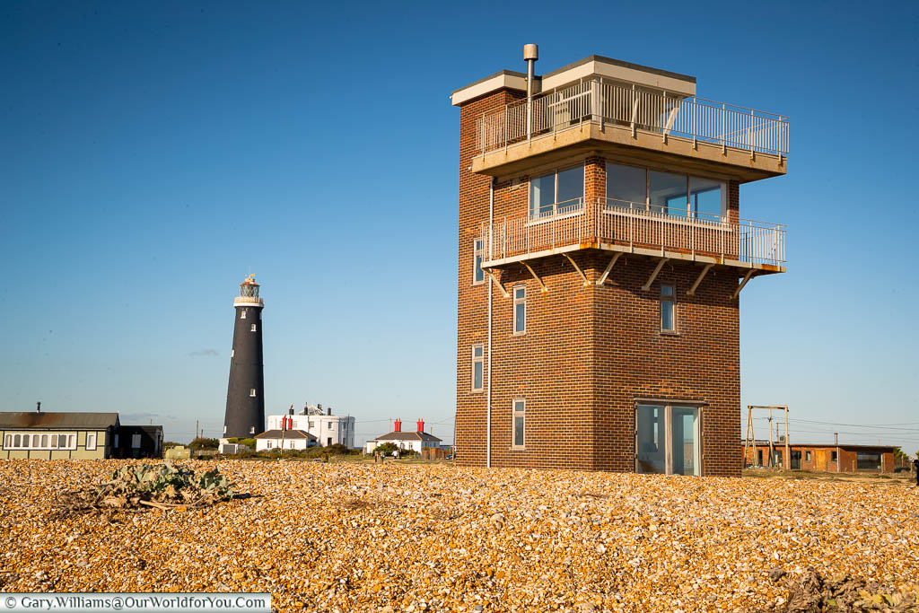 A view of the former brick-built, 10-metre tall Coastguard's tower on the shale beach of Dungeness, with the old lighthouse in the background.