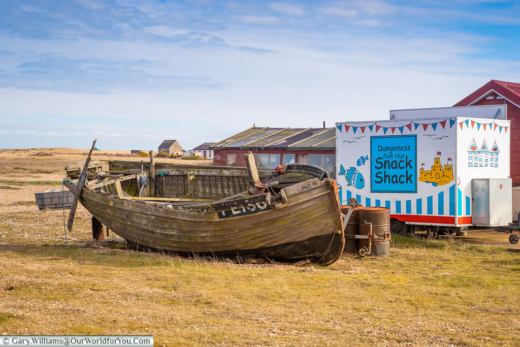 The Dungeness Fish Hut Snack Shack hiding behind a weather-beaten fishing boat on the beach at Dungeness