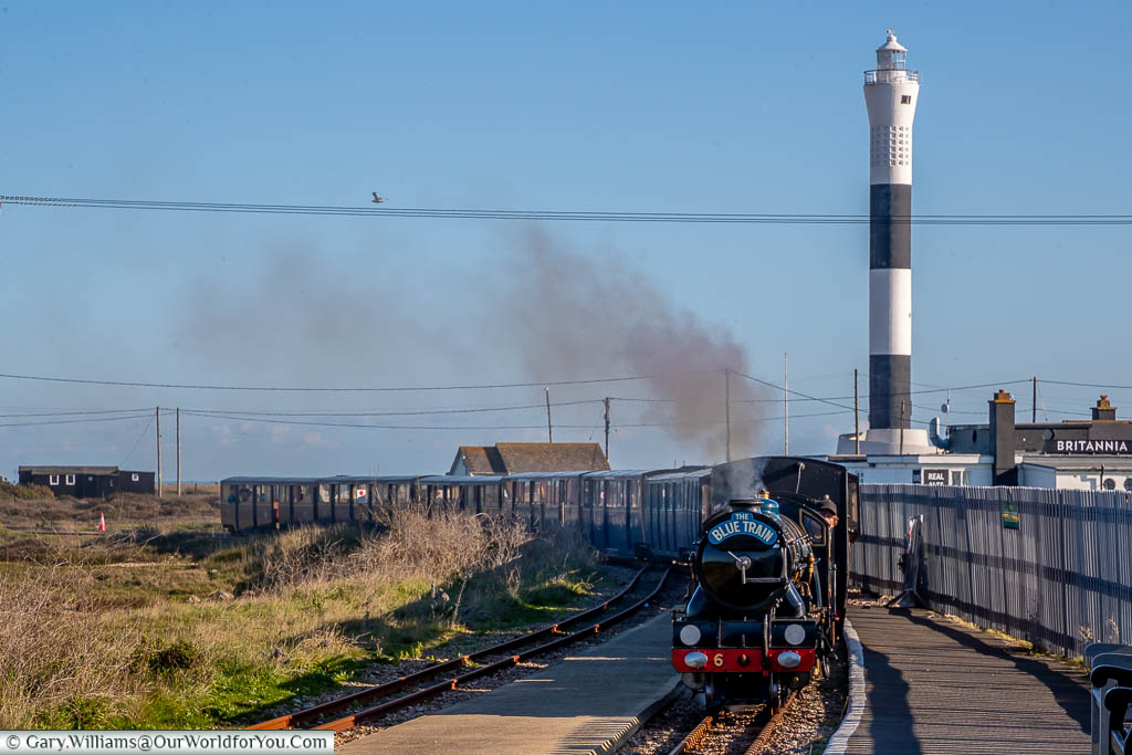 The modern, fifth, tall, Dungeness lighthouse in the background, with the Romney, Hythe and Dymchurch steam train, arriving at Dungeness station in the foreground.