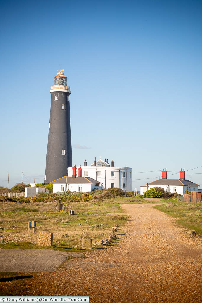 The black tower of Dungeness's forth lighthouse, next to the remaining two-storey white base of the third lighthouse.