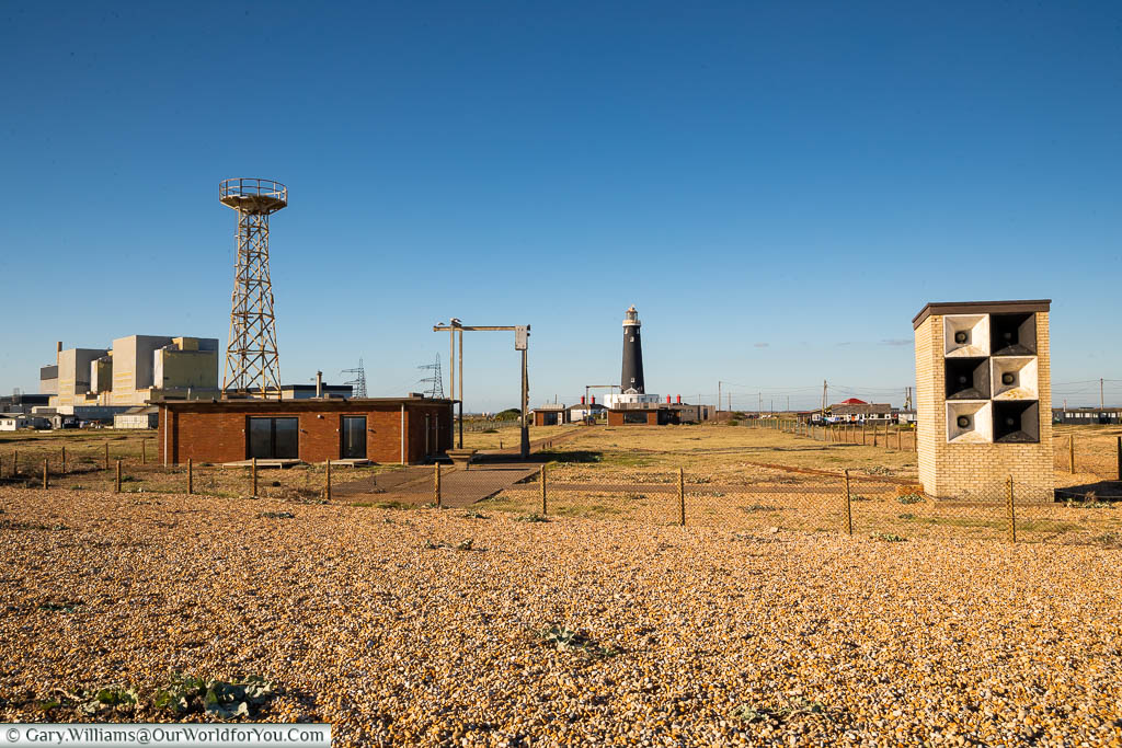 The utilitarian view of Dungeness, with the old lighthouse and power station in the background, and a coastal fog horn array in the foreground